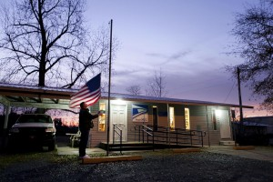 Flint Bradford raises the American flag as the sun rises over the Post Office in Ida, AR. Ida's Post Office is set to close this year.
