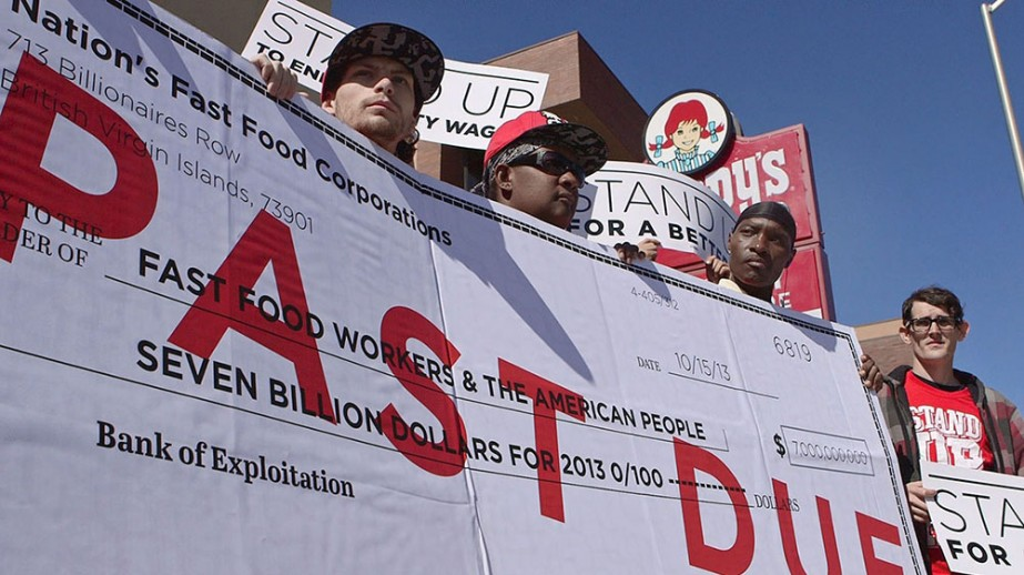 Fast food workers stand outside a Wendy's on Main Street in Kansas City, MO during a press conference discussing the costs to the U.S. taxpayer from the low wages paid by fast food restaurants on Oct. 15, 2013.  The press conference was held to discuss a Univ. of California, Berkeley study that was released that day citing the costs of low wage work in the fast food industry.